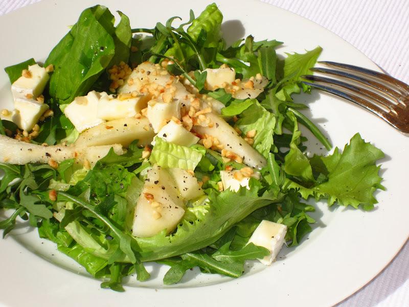 insalata di foglie verdi, pera e brie su piatto bianco