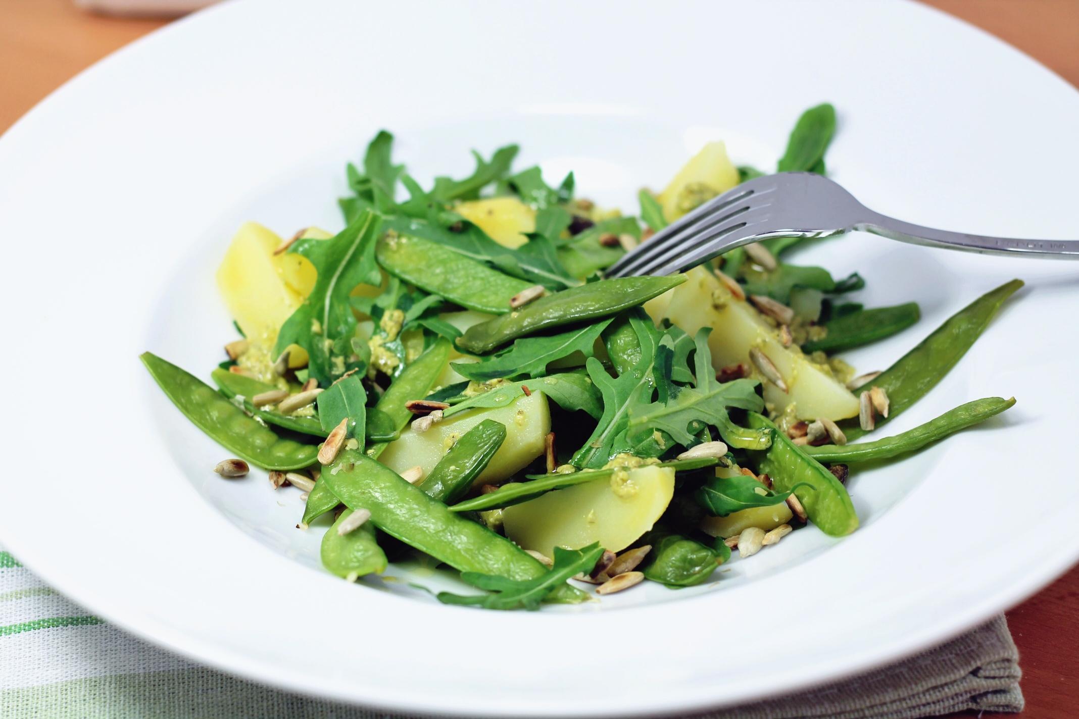 Foto con insalata di taccole, patate e rucola su piatto bianco
