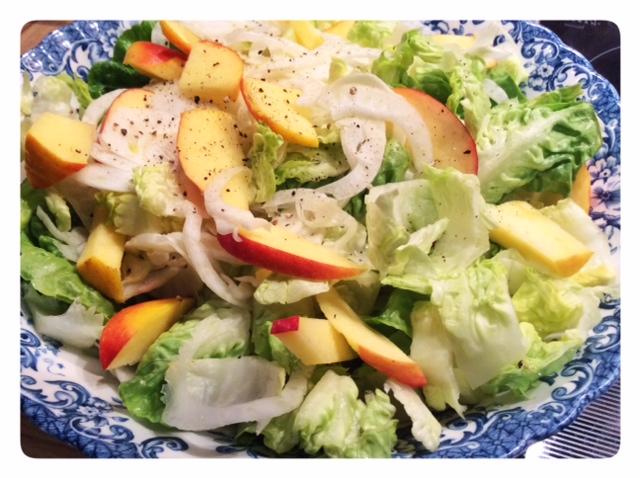 Nella foto si vede un'insalatiera con una ricca insalata con mele e lattuga condita con aceto alle arance