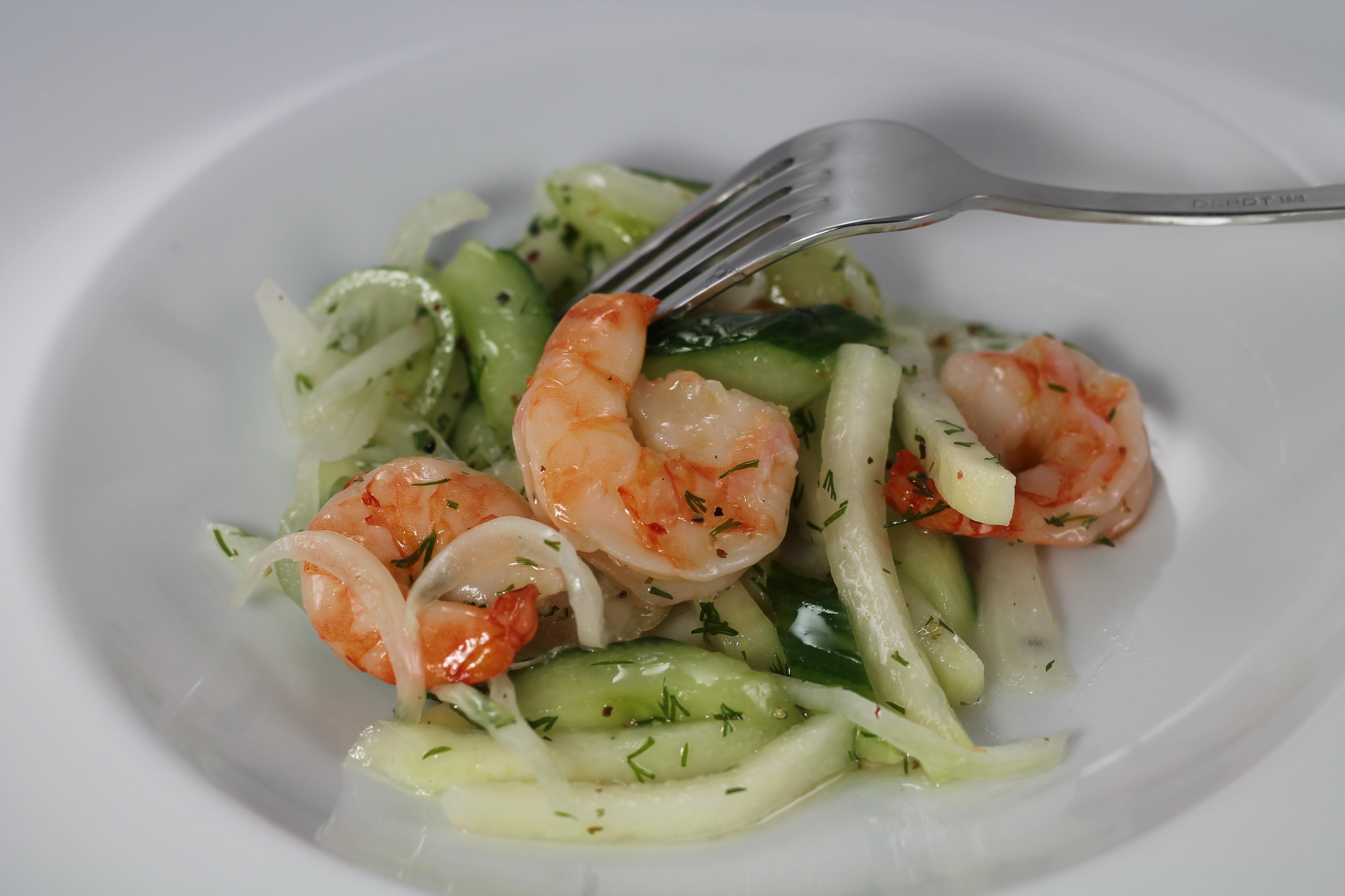 Nella foto si vede un'insalata di scampi, cavolo rapa e cetriolo su un piatto bianco