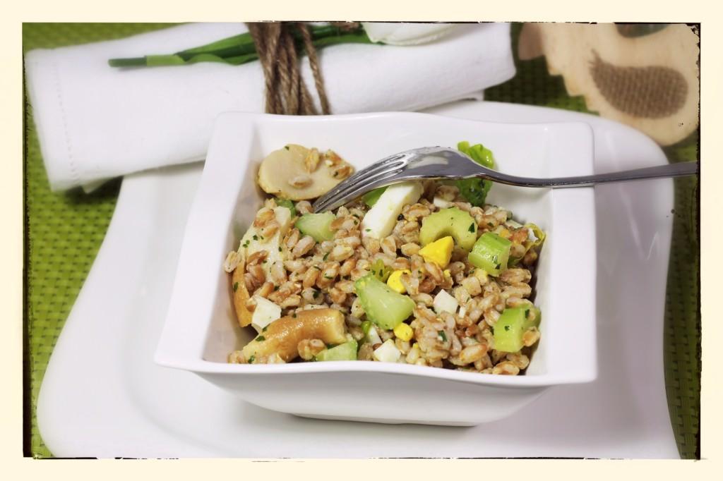 Nella foto si vede un'insalata di farro, funghi e sedano in una ciotola bianca