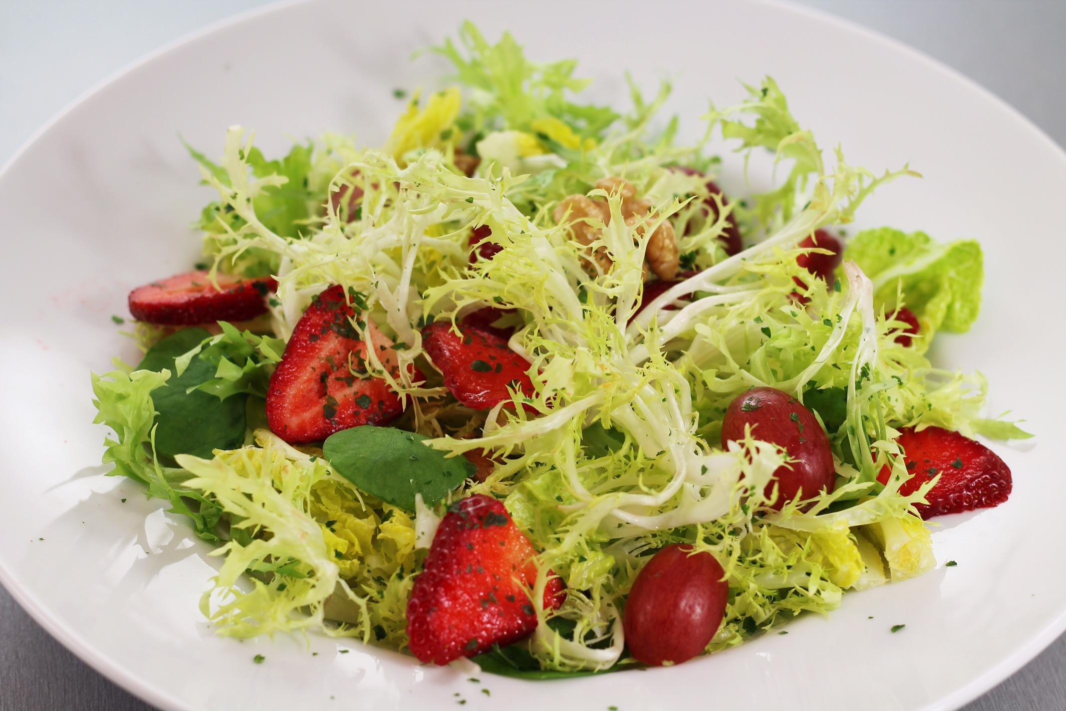 Nella foto si vede un piatto bianco con un'insalata coloratissima con fragole