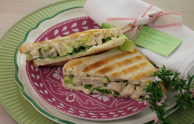 Nella foto si vedono due sandwich a base di insalata di pollo su un piatto rosa