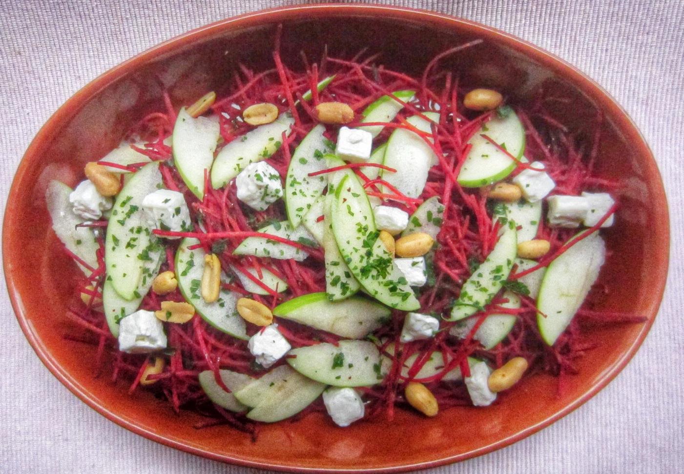 Nella foto si vede una pirofila contenente un'insalata di barbabietole, mela e arachidi