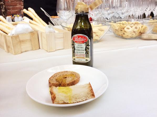 nella foto si vedono due fette di pane su un piatto accanto a una bottiglia d'olio
