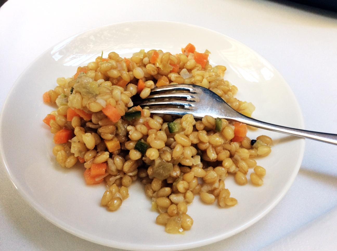 Foto di un piatto bianco con insalata di grano