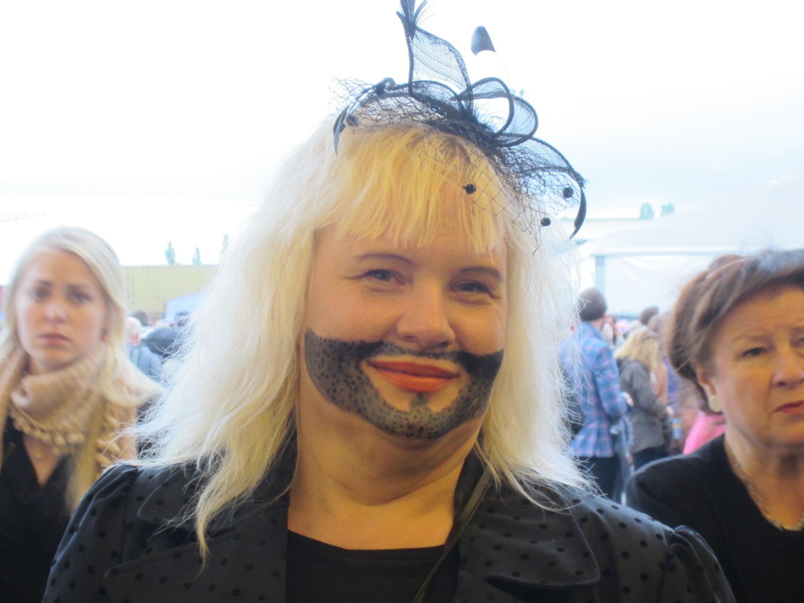 Primo piano di donna bionda con barba dipinta