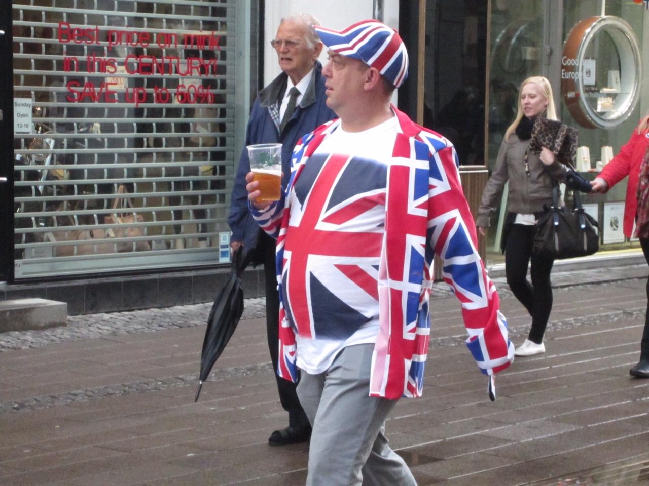 Uomo vestito con giacca e maglietta riproducenti la bandiera britannica