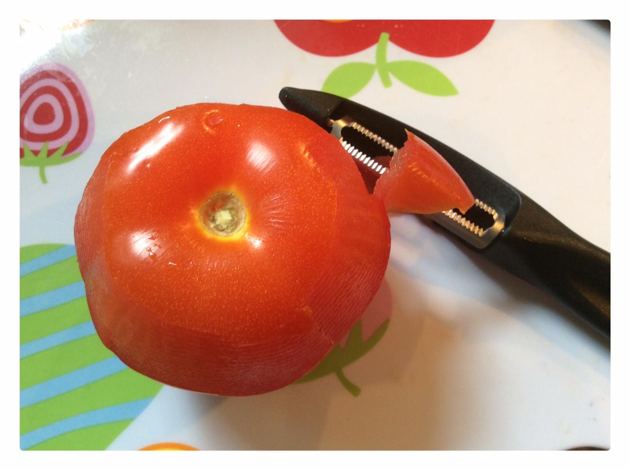 Nella foto si vede la pelatura di un pomodoro con un pelapomodori