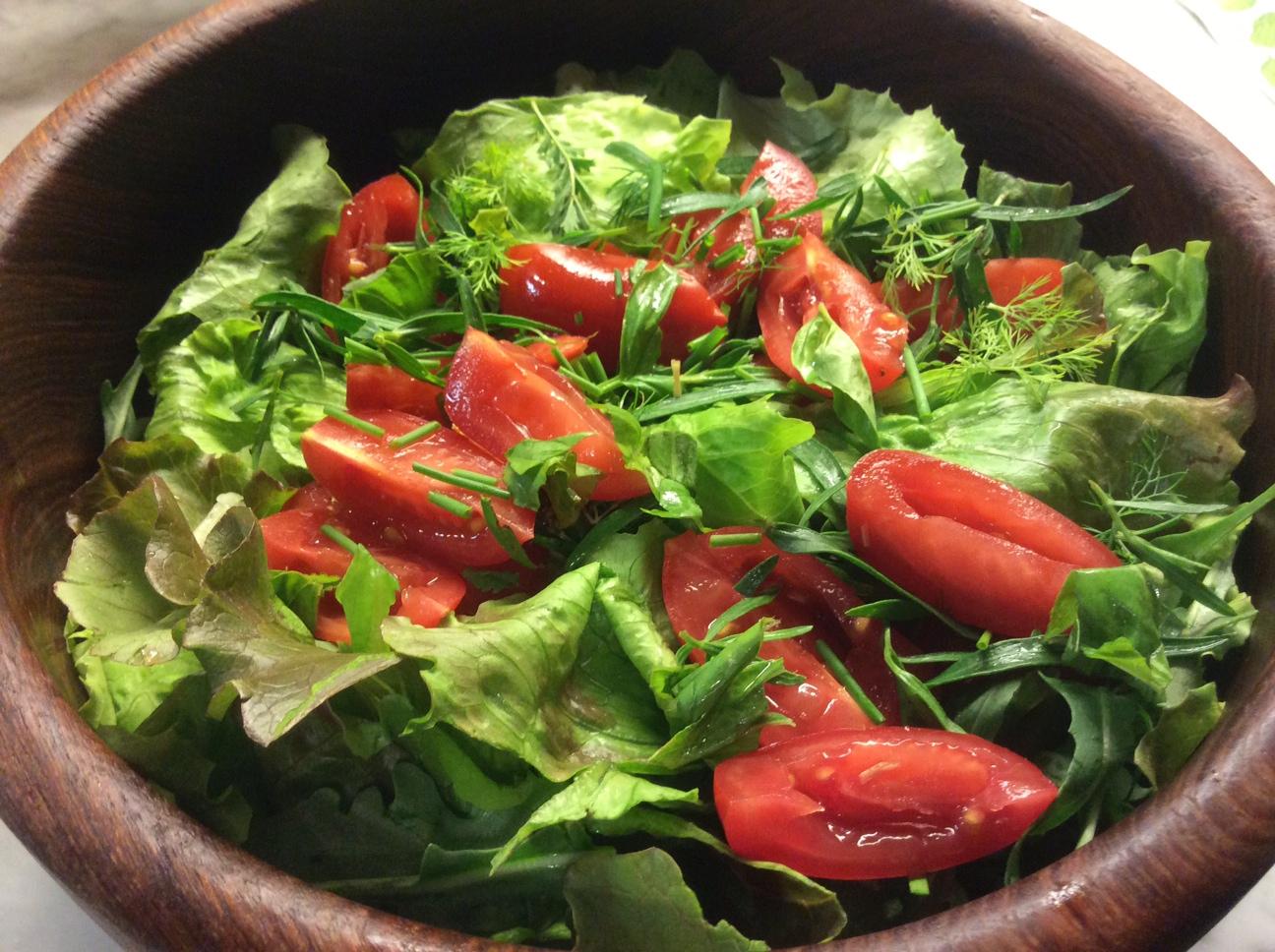 Nella foto si vede un'insalata di lattuga, pomodori ed erbe
