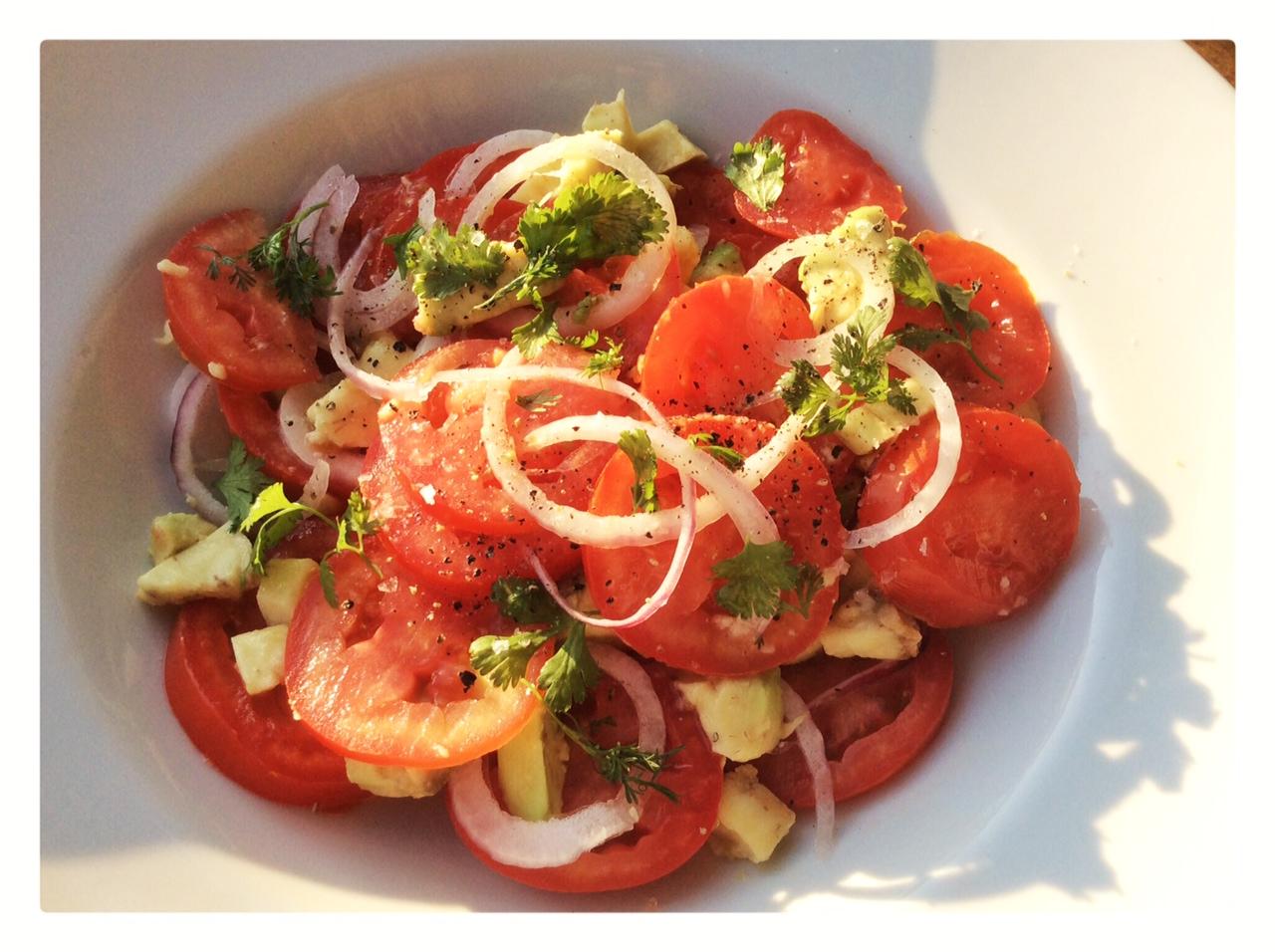 piatto con insalata di pomodori, cipolle, avocado e foglie verdi