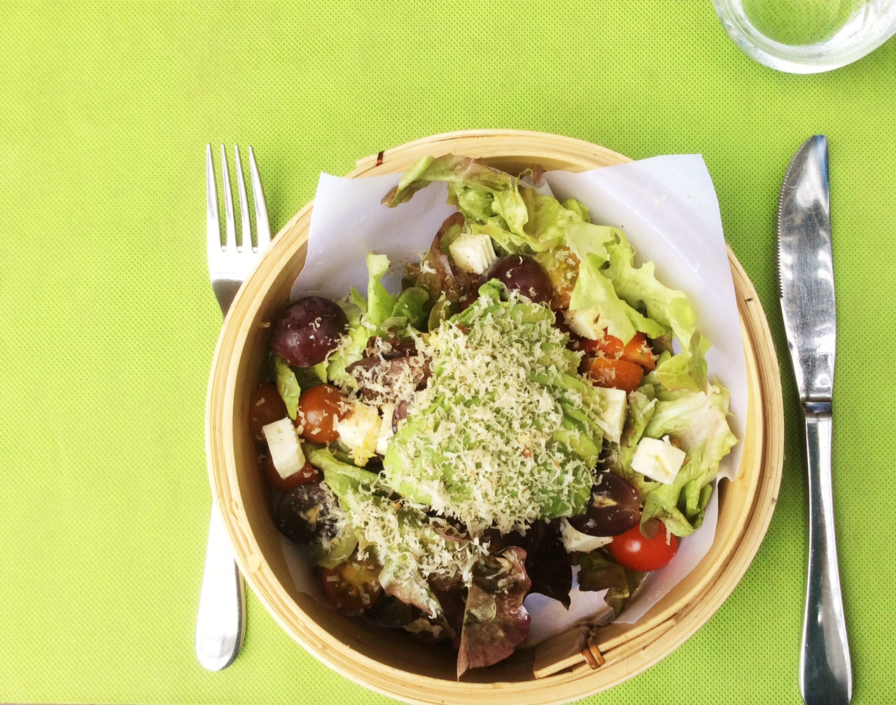 Foto di un'insalata in un cestino, su fondo verde