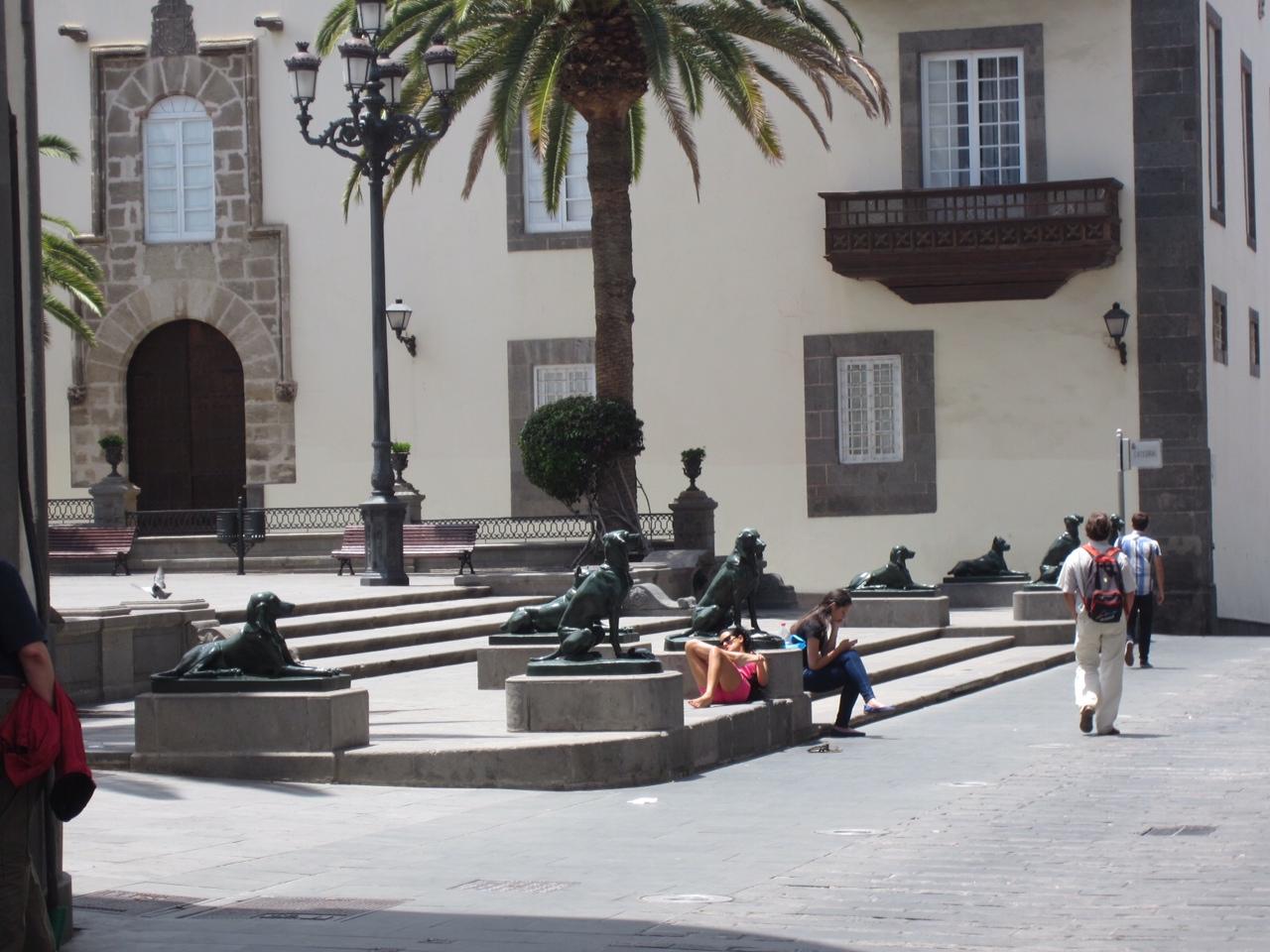Gruppo di cani di bronzo tra passanti