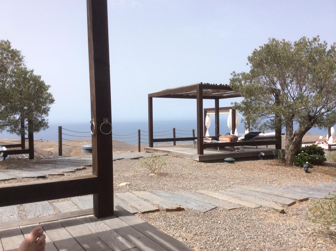 Letti balinesi, olivi e oceano sullo sfondo