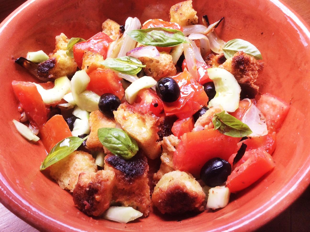 Terrina in terracotta contenete insalata di crostini di focaccia, pomodori, cetrioli e cipolle