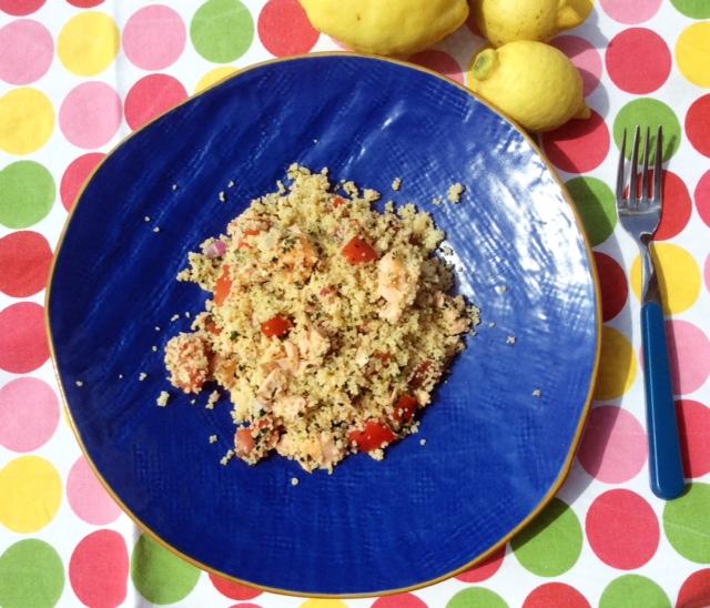Insalata di cous cous al salmone su piatto blu su tovaglia colorata