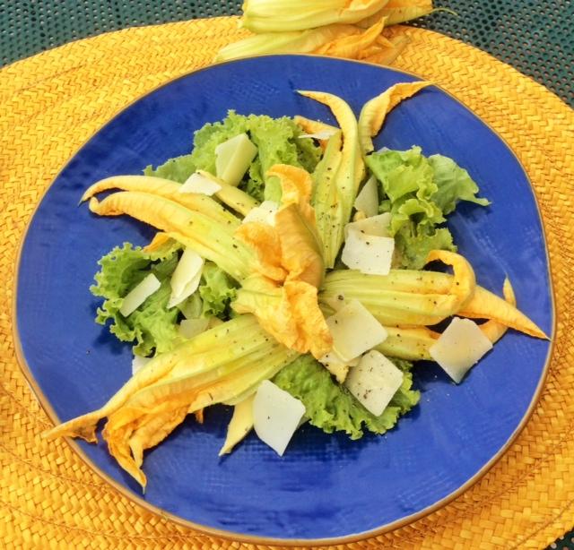 Piatto blu con insalata con fiori di zucchina