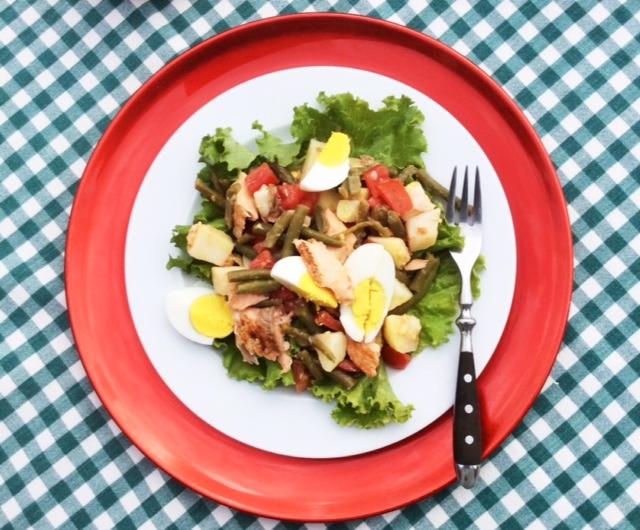 salade niçoise con salmone su piatto bianco e sottopiatto rosso