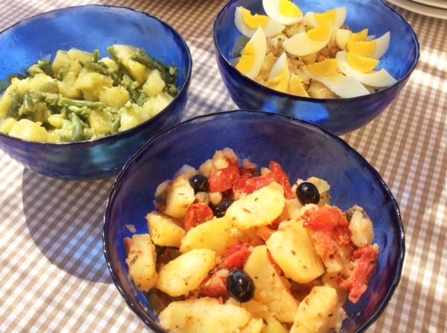 Tre ciotole insalate di patate in ciotole blu