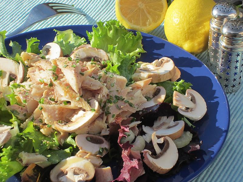 Insalata con champignon e filetti di trota affumicata  su piatto blu