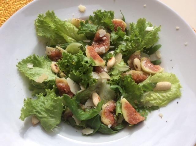 Piatto bianco con insalata verde con  fichi e mandorle