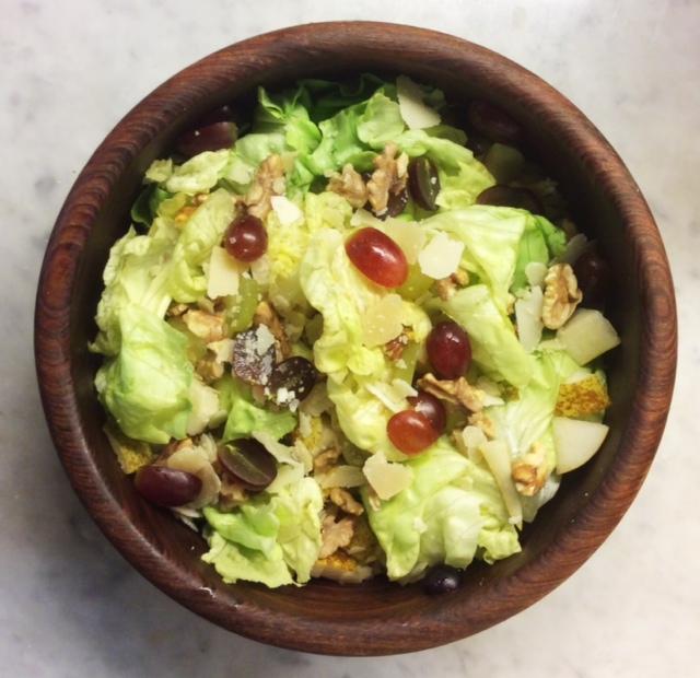 Insalatiera tonda in legno contenete insalata di lattuga con uva e noci