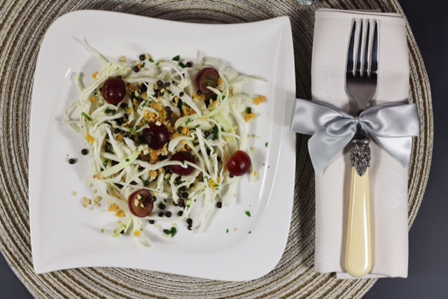 piatto bianco con insalata di cavolo,lenticchie e uva