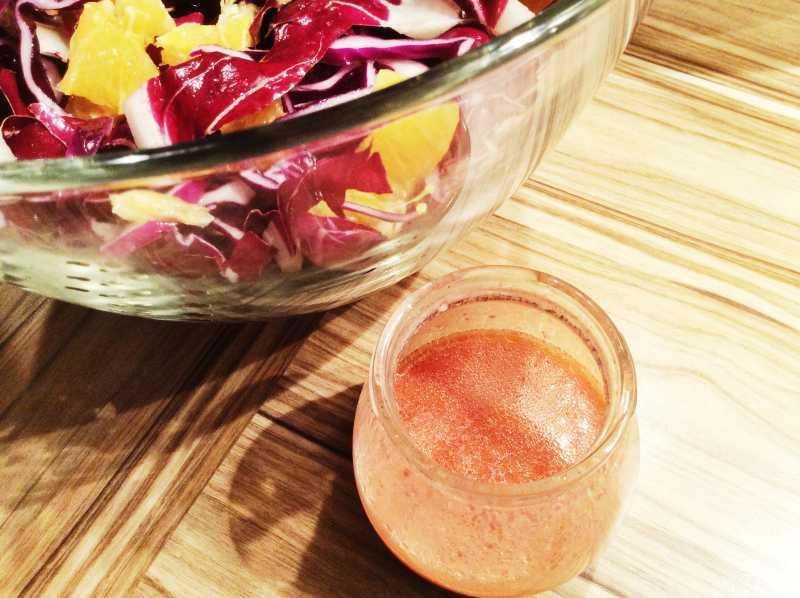 insalatiera di vetro con insalata di radicchio e vasetto con vinaigrette