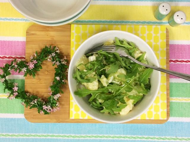insalata di patate e rucola in ciotola bianca su tovaglietta a righe
