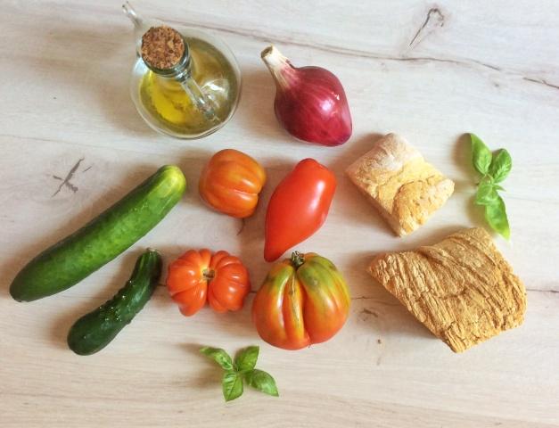 pomodori, pane cetriolo e olio su piano di legno bianco