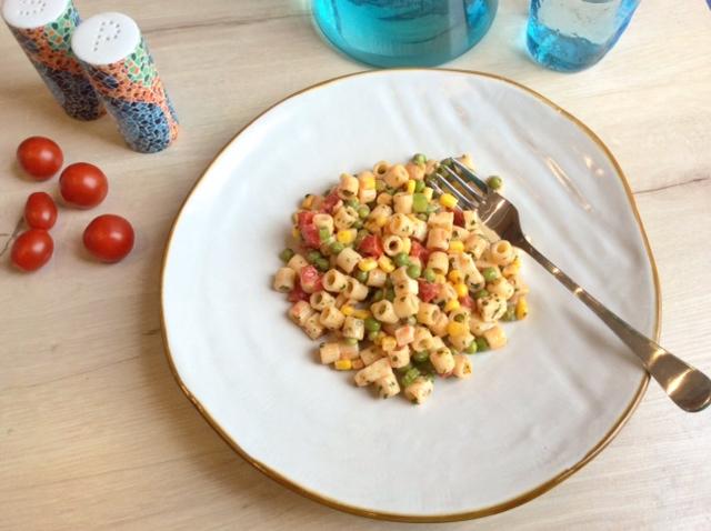 insalata di pasta con piselli su piatto bianco