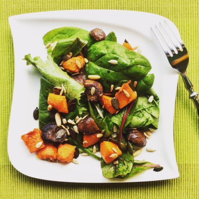 insalata con zucca e foglie verdi su piatto bianco