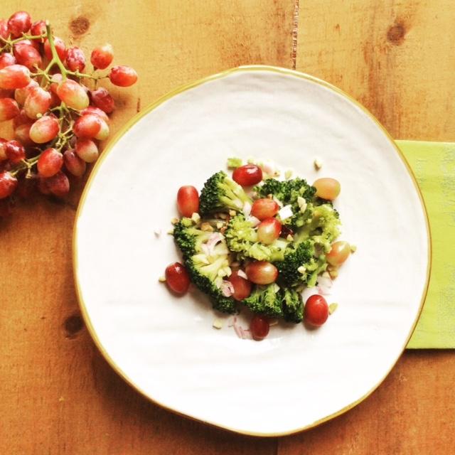 insalata di broccoli e uva rosata su piatto bianco