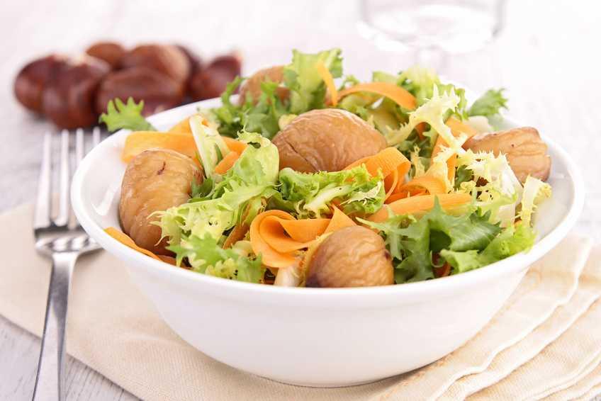 insalata con foglie verdi, castagne e carote in ciotola bianca