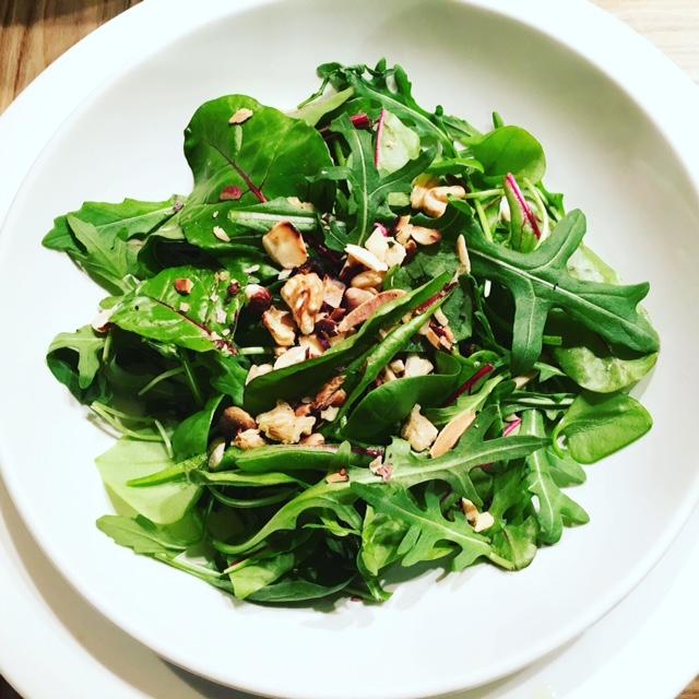 insalata leggerissima di foglie verdi e noci tritate su piatto bianco