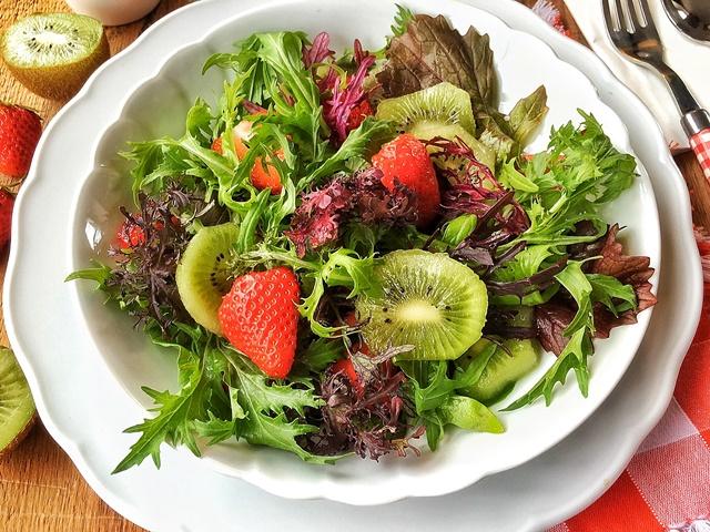 insalata di misticanza con kiwi e fragole in piatto bianco
