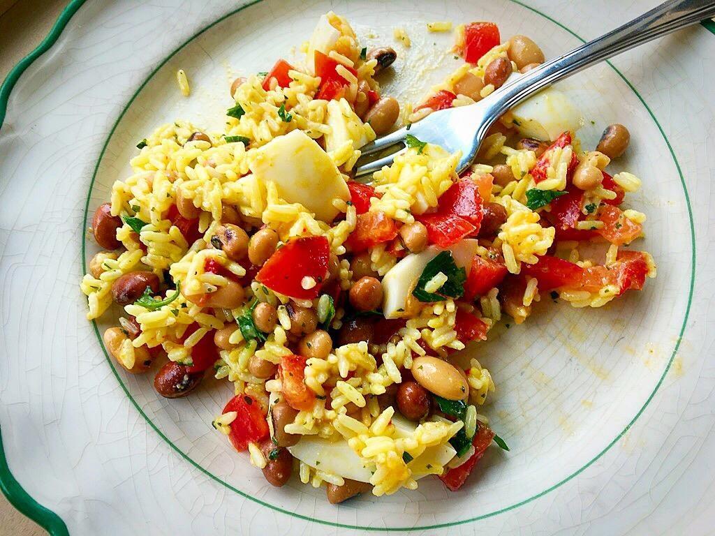 una sostanziosa insalata di riso su piatto, con forchetta tra i chicchi