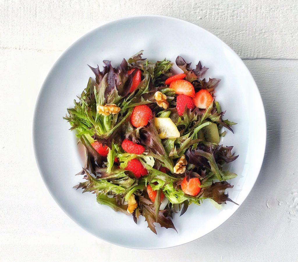 insalata di lattuga sweet crisp rossa con fragole, lamponi e kiwi su piatto bianco