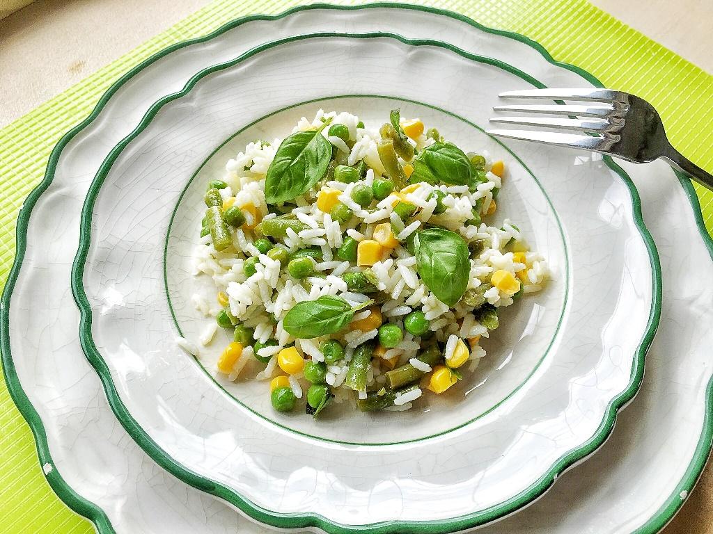 insalata di riso vegetaraina con piselli e mais su piatto con bordo verde