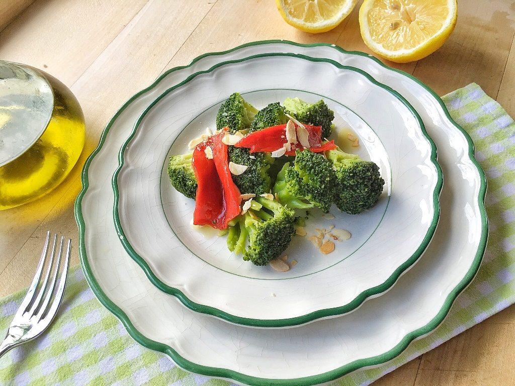 insalata tiepida di broccoli e peperoni su piatti bianchi
