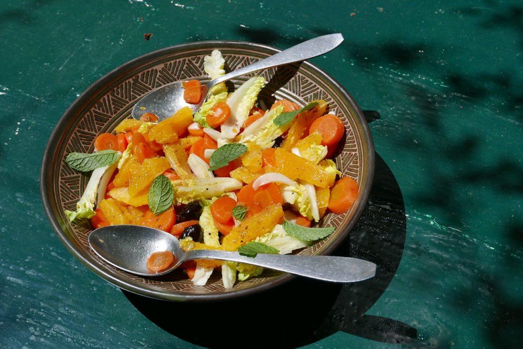 Arance in insalata con cuori di lattuga romana, carote e olive in piatto scuro