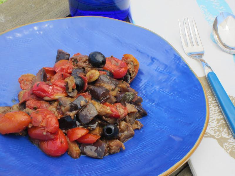 insalata di melanzane, olive e pomodori su piatto blu