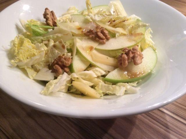 Insalata di verza e mela con noci su piatto bianco