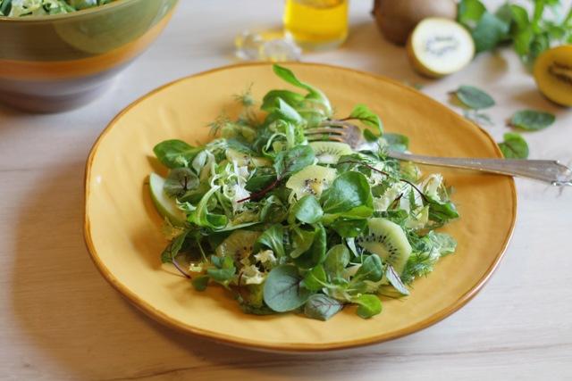 Insalata con aneto e kiwi su piatto giallo