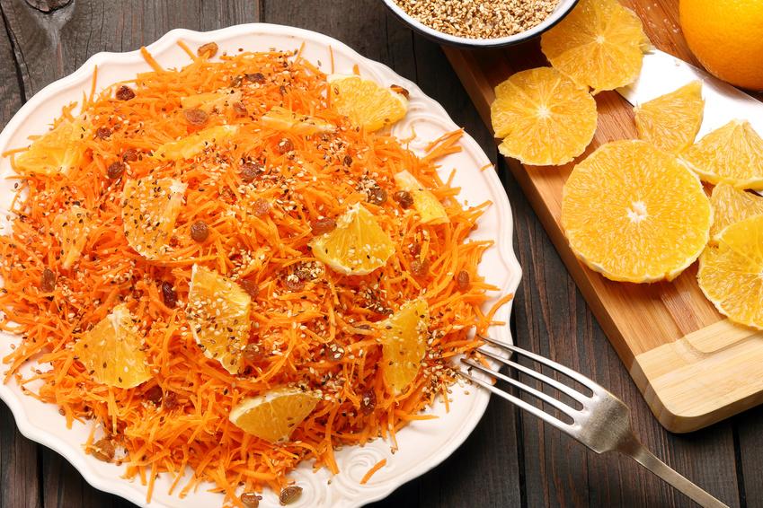 Insalata di carote e arance con sesamo su piatto bianco