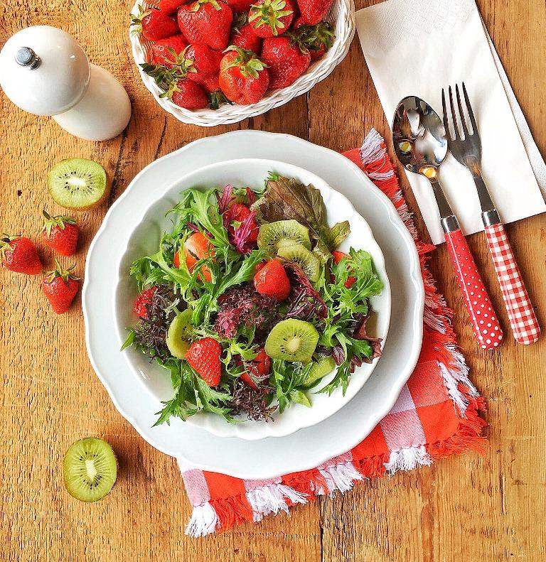 insalata con kiwi e fragole in piatto bianco su piano di legno