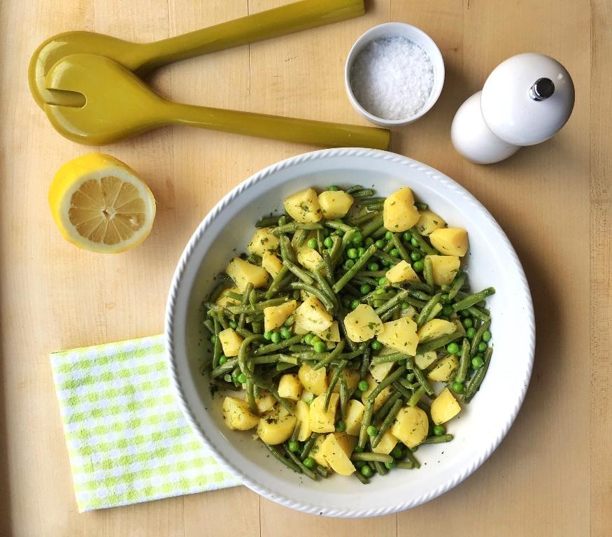 insalata di patate e fagiolini e piiselli in ciotola bianca accanto a mezzo limone